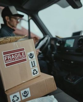 A box of a fragile item sitting in the front seat of a delivery truck